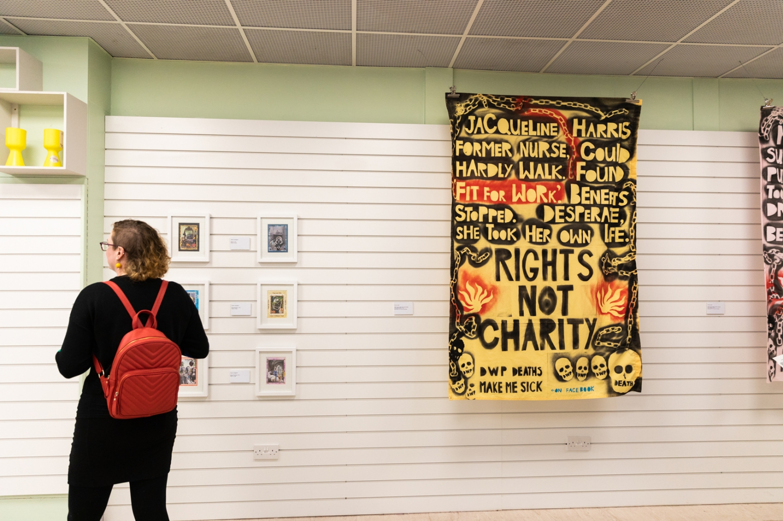 """Inside the exhibition, a woman reads the introductory text to her left (the text is out of shot). Before her on the wall, Sasha Callaghan's series of 6 digital collages, framed and in 3 rows of 2. To the right is one of Vince Laws' stencilled shrouds, the prominent message reading """"RIGHTS NOT CHARITY""""."""